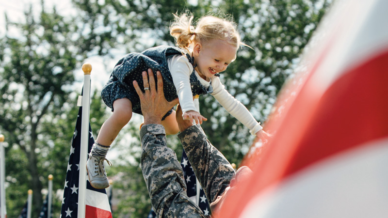 military father holding smiling child in arms